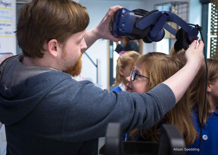 STEM Leader putting a VR headset on a child
