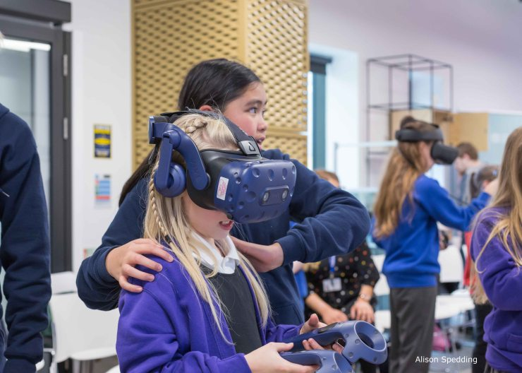 A pupil helping another pupil wearing a VR Headset