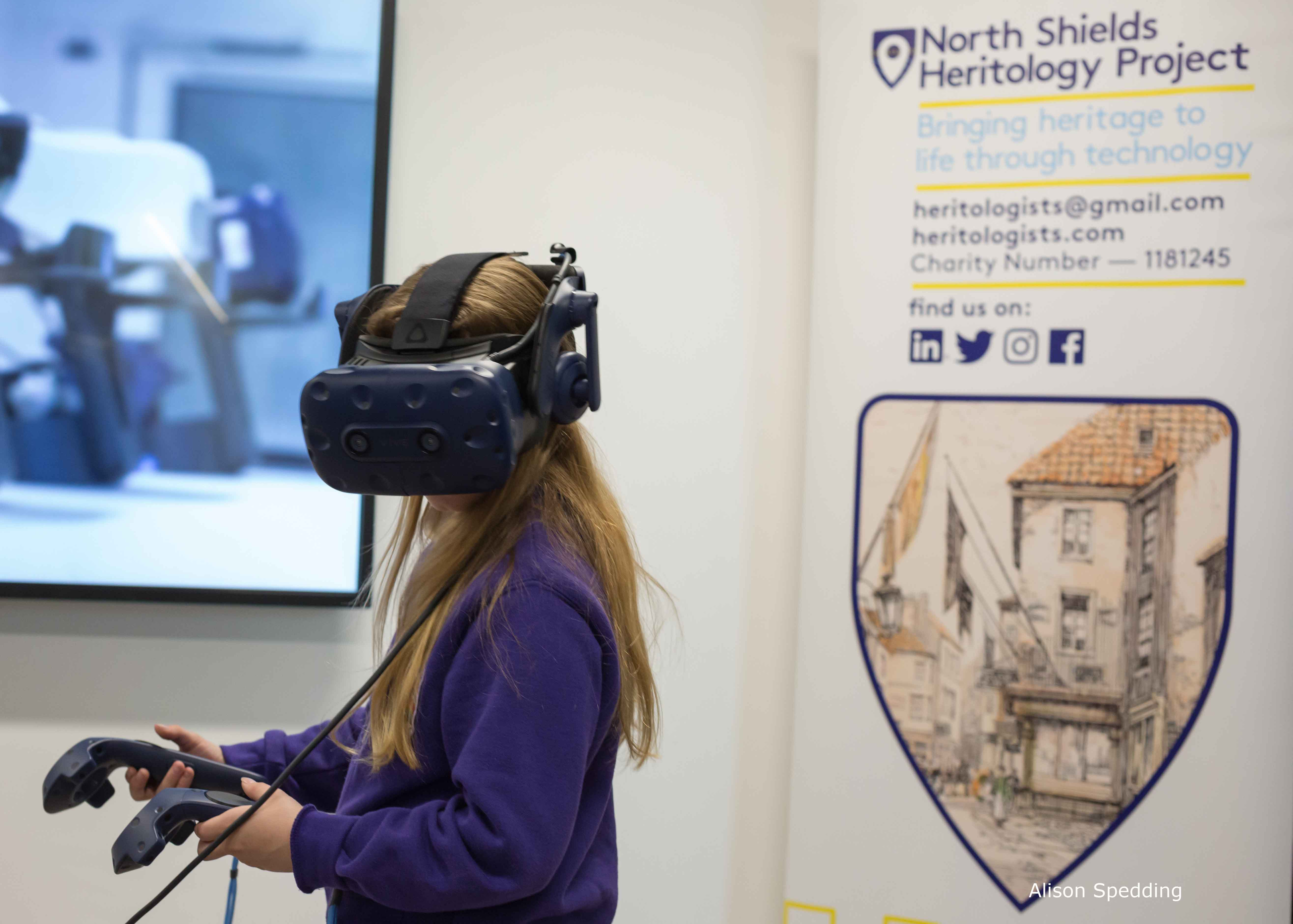 A child wearing a VR headset in front of the North Shields Heritology banner stand