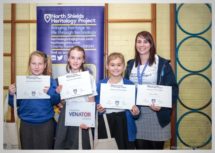 A group of children and teacher holding their Heritology Certificates