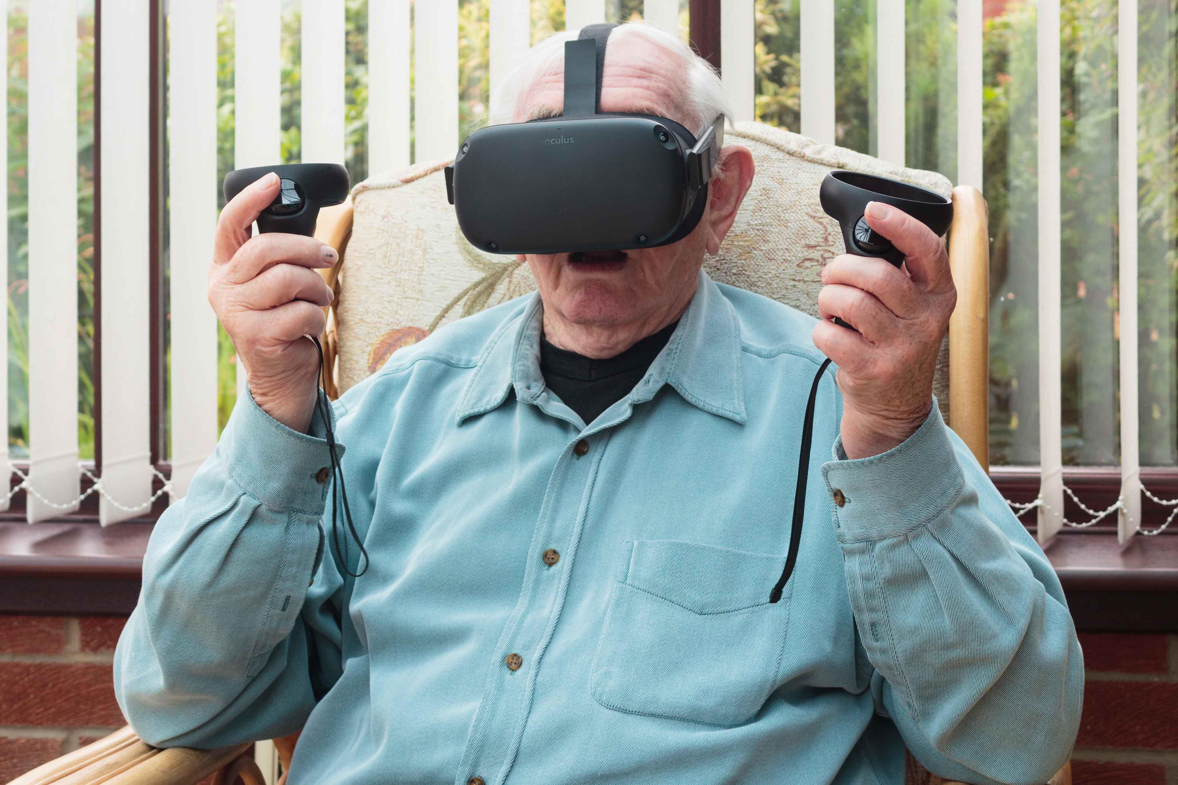 Elderly man dsat in a chair wearing a VR headset